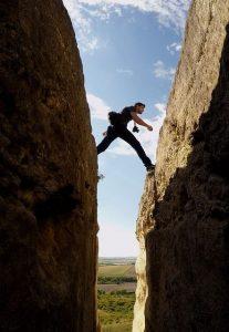 Mann, der einen Spalt im Berg überschreitet